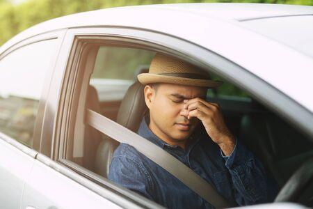 Drunk young man slumped on steering wheel be tired sleep in car driving. Foto de archivo