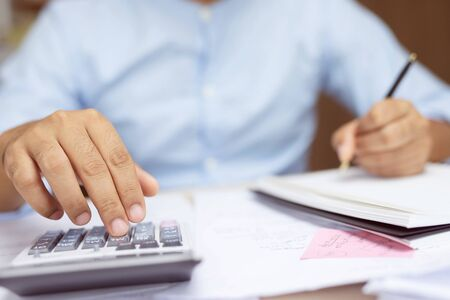 Close up business man hand is writing in a notebook and using calculator counting making notes Accounting at doing finance at office. Savings finances concept. note pad. Leave space for writing text. Stock Photo