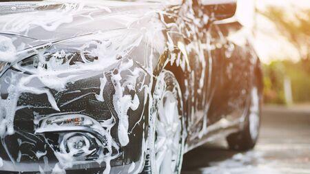 Lavado de autos al aire libre con jabón en espuma activo. concepto de servicio de lavado de limpieza comercial. Foto de archivo