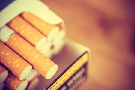 image of several commercially made cigarettes. pile cigarette on wooden. or Non smoking campaign concept, tobacco. filter vintage retro. 스톡 콘텐츠