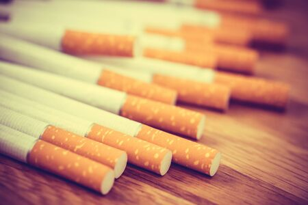 image of several commercially made cigarettes. pile cigarette on wooden. or Non smoking campaign concept, tobacco. filter vintage retro. Stock Photo