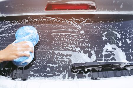 people man worker holding hand blue sponge for washing car. Concept car wash clean. soft focus.