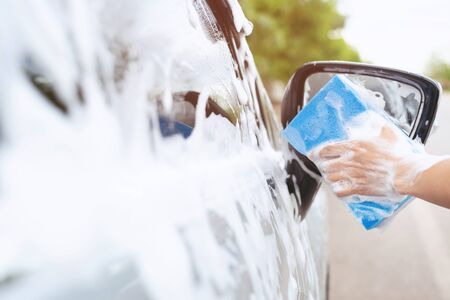 people worker man holding hand blue sponge and bubble foam cleanser for washing car. Concept car wash clean. Leave space for writing messages.