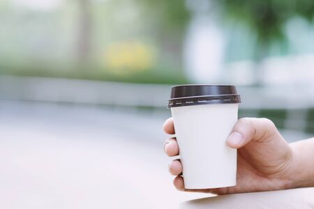 hand holding paper cup of take away drinking coffee on natural morning sunlight. space Place for your text or logo