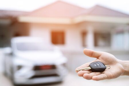 Business man hand holding car keys front with new car on background. parking in front of the house. transportation concept. Leave copy space to write messages text. Stockfoto