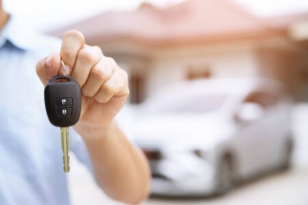 Businessman hand holding car keys front with new car on background. parking in front of the house. transportation concept. Leave copy space to write messages text.