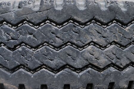 close up old damaged and worn black tire tread truck. Tire tread problems and solutions for road safety concept. Change time. transportation. Write text in the texture background and backdrop. 写真素材