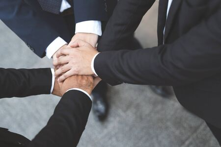 Close up of Group people of businessmen joining putting their hands together with stack of hands showing unity and teamwork. concept Success and encouragement to overcome obstacles. soft focus. 写真素材