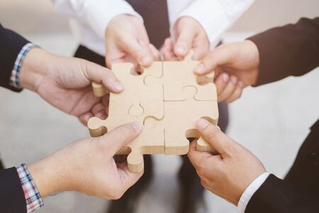 three businessman hand hold trying to connect Jigsaw wooden puzzle piece stand floor office background. one part of whole. symbol of association and connection. success and business solution strategy