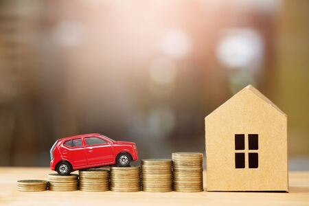 Saving money, Little toy car, money coins stacked on each other in different positions, house in paper model on the wooden table. Credit financial growing Loan to buy real asset concept.