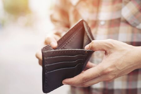 Empty wallet (no money) in the hands of an man. Cost control expenses poverty in concept. Leave space to write descriptive text.
