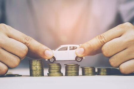 Business man and close up hand holding model of toy car white on over a lot money of stacked coins - insurance, loan and buying car finance concept. buy and installments down payment a car.