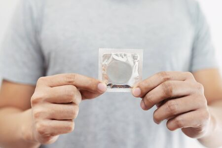 Condom ready to use in male hand, give condom safe sex concept on the bed Prevent infection and Contraceptives control the birth rate or safe prophylactic. World AIDS Day, Leave space for text.
