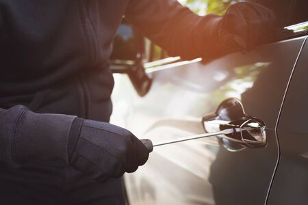 Close up car thief wearing black clothes hand holding screwdriver tamper yank and glove stealing automobile trying door handle to see if vehicle is unlocked trying to break into. car theft concept. 写真素材