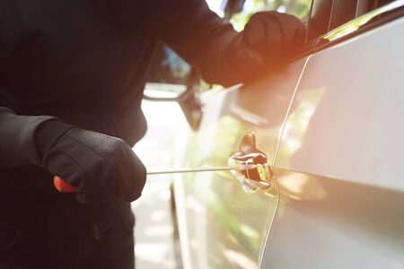 car thief a man in a hooded top black clothes and wear gloves breaking into a car door trying to break into with a screwdriver in order to steal it. Lost car insurance concept