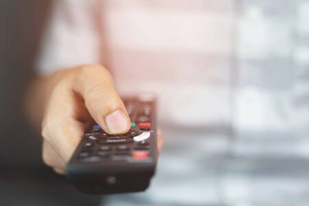 close up Television remote control in casual man hands pointing to tv set and turning it on or off. select channel watching tv on his sofa at home in the living room relax. soft focus.