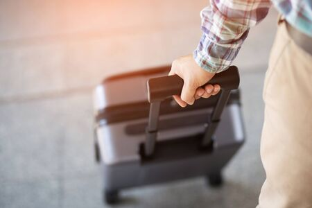 businessman walking outside public transport building with luggage in rush hour. Business traveler pulling suitcase in modern airport terminal. baggage business Trip. Copy space , top view Stock fotó