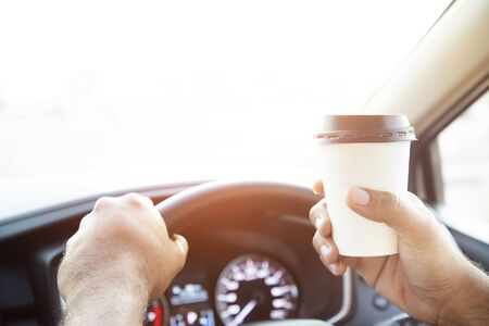 people person drinking paper cup coffee of hot holding hand in a car in the morning not sleepy be energetic while driving. transportation and vehicle concept. empty copy space for text.