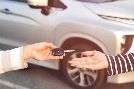 Car key, young man handing over gives the car key to the other man on car background. transportation and vehicle concept. Leave space for writing text.