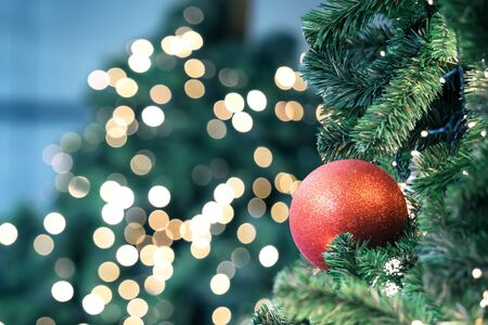 Closeup of red bauble hanging from a decorated christmas tree on blurred of lights with decorated tree, sparkling and bokeh background. copy space for your text. Zdjęcie Seryjne