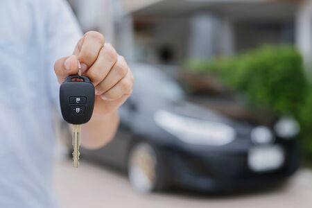 Geschäftsmannhand, die Autoschlüsselfront mit neuem Auto auf Hintergrund hält. Parkplatz vor dem Haus. Transportkonzept. Lassen Sie Kopienraum, um Nachrichtentext zu schreiben. Standard-Bild