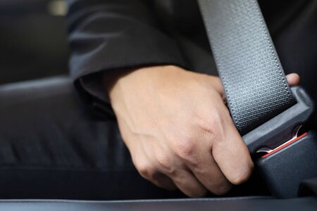 Close Up of people business man hand fastening seat safety belt in car for safety before driving on the road. concept transport travel. soft focus
