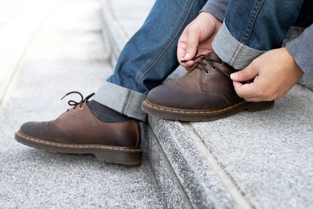 people man in jeans tie up shoelace on wearing brown leather shoes sitting staircase background. Mens lifestyle. Leave space for writing descriptive text.