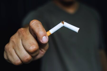 Man refusing cigarette holding in hand concept for quitting smoking and healthy lifestyle.or No smoking campaign Concept. dark black background.