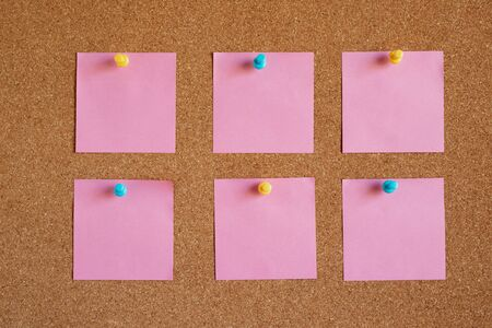 collection of pink pastel variety post. paper note reminder sticky notes pad push pin color blue yellow on cork bulletin board. empty space for text.