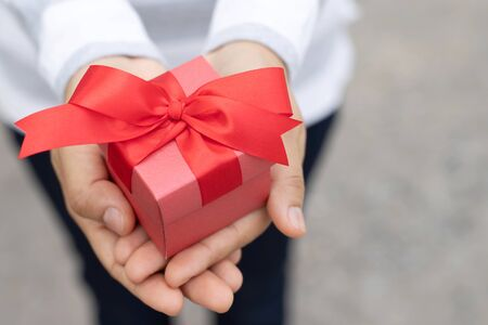 female hands holding gift box red wrapped pack with beautiful ribbon. outdoor background. for surprise special event with copy space. Christmas, birthday or new year concept. High resolution product.