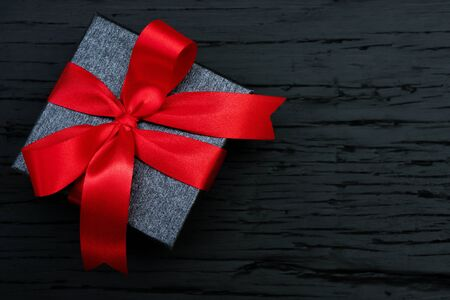 gift box white new year or Christmas Packed present container with red ribbon on Vintage Matte black wooden board background for holiday concept with copy space, top view.