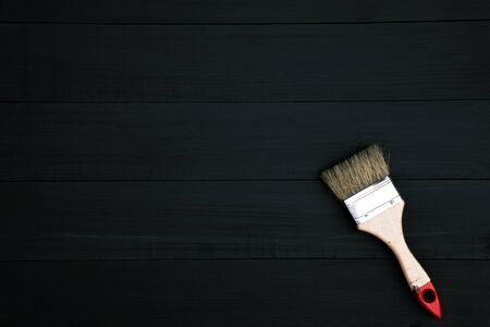 paint brush lying on wooden clean table. Dark black background. Top view. Leave Copy space to write a message.