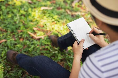 close up hand young man are sitting using pen writing Record Lecture notepad into the book in the park. Top view Zdjęcie Seryjne