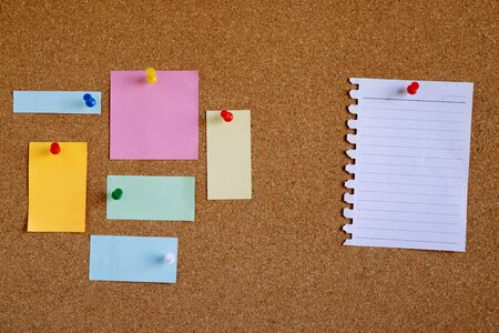 Piece paper of blank white note pad reminder and collection of colorful variety post. stick colorful push pin to a cork bulletin board. empty space for text write a note. Zdjęcie Seryjne