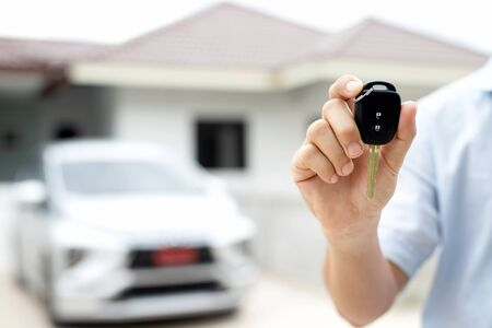 Business man hand holding car keys front with new car on background. parking in front of the house. transportation concept. Leave copy space to write messages text. Zdjęcie Seryjne