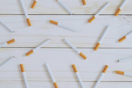 image of several commercially made pile cigarette on white wooden background. or Non smoking campaign concept, tobacco pattern top view.