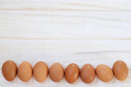 Huevos de gallina frescos desde arriba sobre un fondo de madera blanca. Patrón de espacio de texto. Foto de archivo