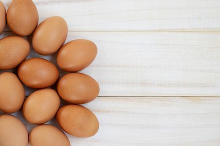 fresh chicken eggs from above on a white wooden background. Text space pattern.