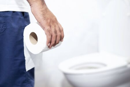 man suffers from diarrhea holds toilet paper roll in front of toilet bowl. Stomach