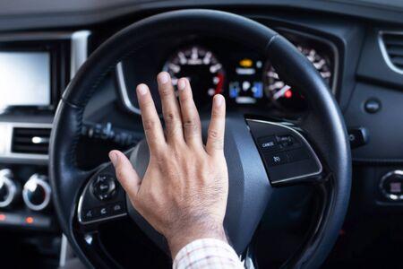 Man honking car horn for safety