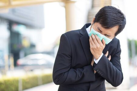 A business man wears a mask to protect Corona virus before going to work at the office.