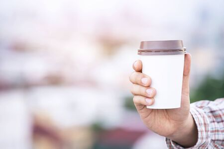 Mockup of male hand holding a Coffee paper cup isolated Фото со стока