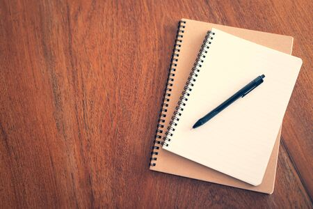 notebook with pen and pencil on wooden table