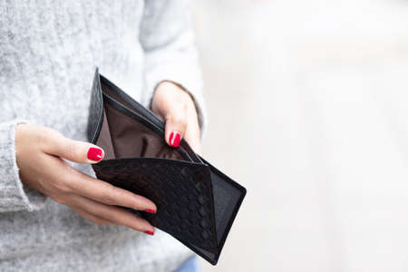 A woman carrying a wallet while shopping at a mall