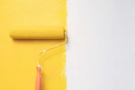 The painter is painting the yellow wall room.