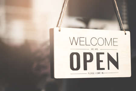 A business sign that says 'Open' on cafe or restaurant hang on door