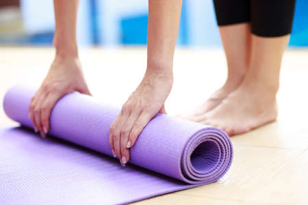 Close-up of attractive young woman folding blue yoga or fitness mat after working out at home in living room. Standard-Bild