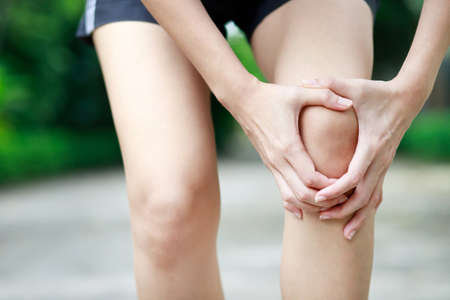 A woman with a lot of knee pain in the park