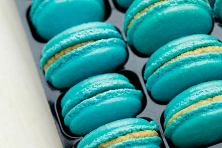 Sweet blue French macarons are in the bakery.