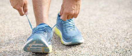 Runners tie their shoes on the running course.